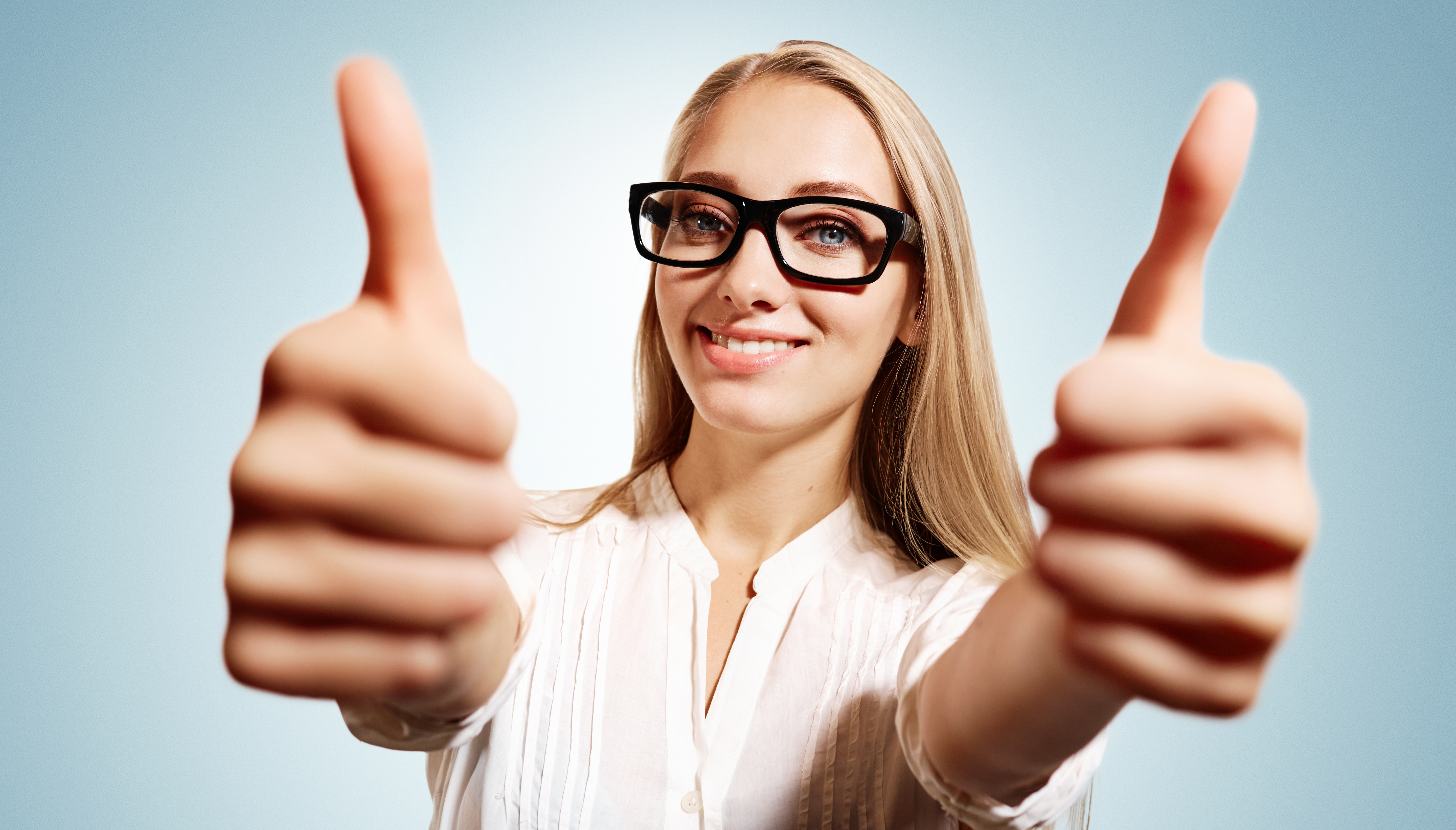 Closeup portrait handsome young smiling blonde business woman, corporate employee giving thumbs up sign at camera at blue background. Positive human emotions, facial expression, feelings.