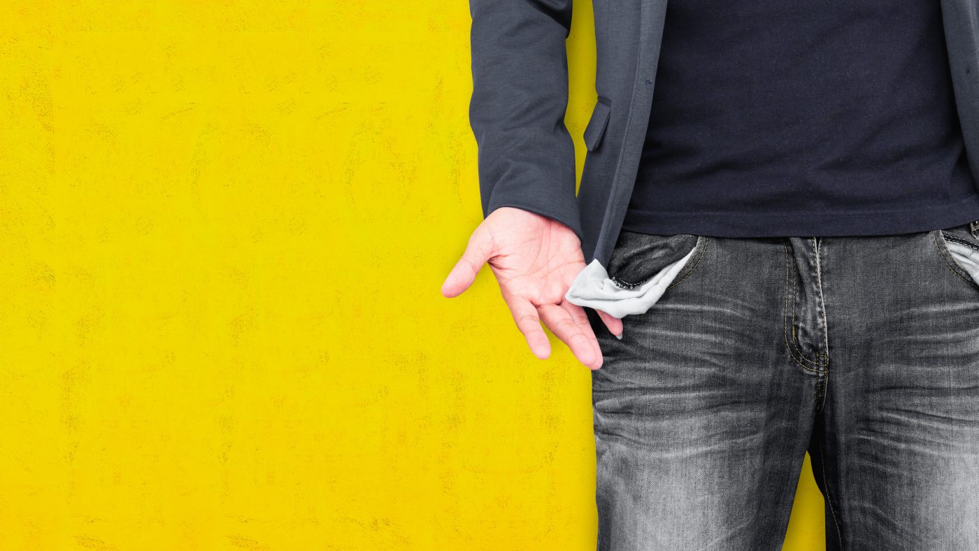 Man showing his empty pockets on yellow wall background.