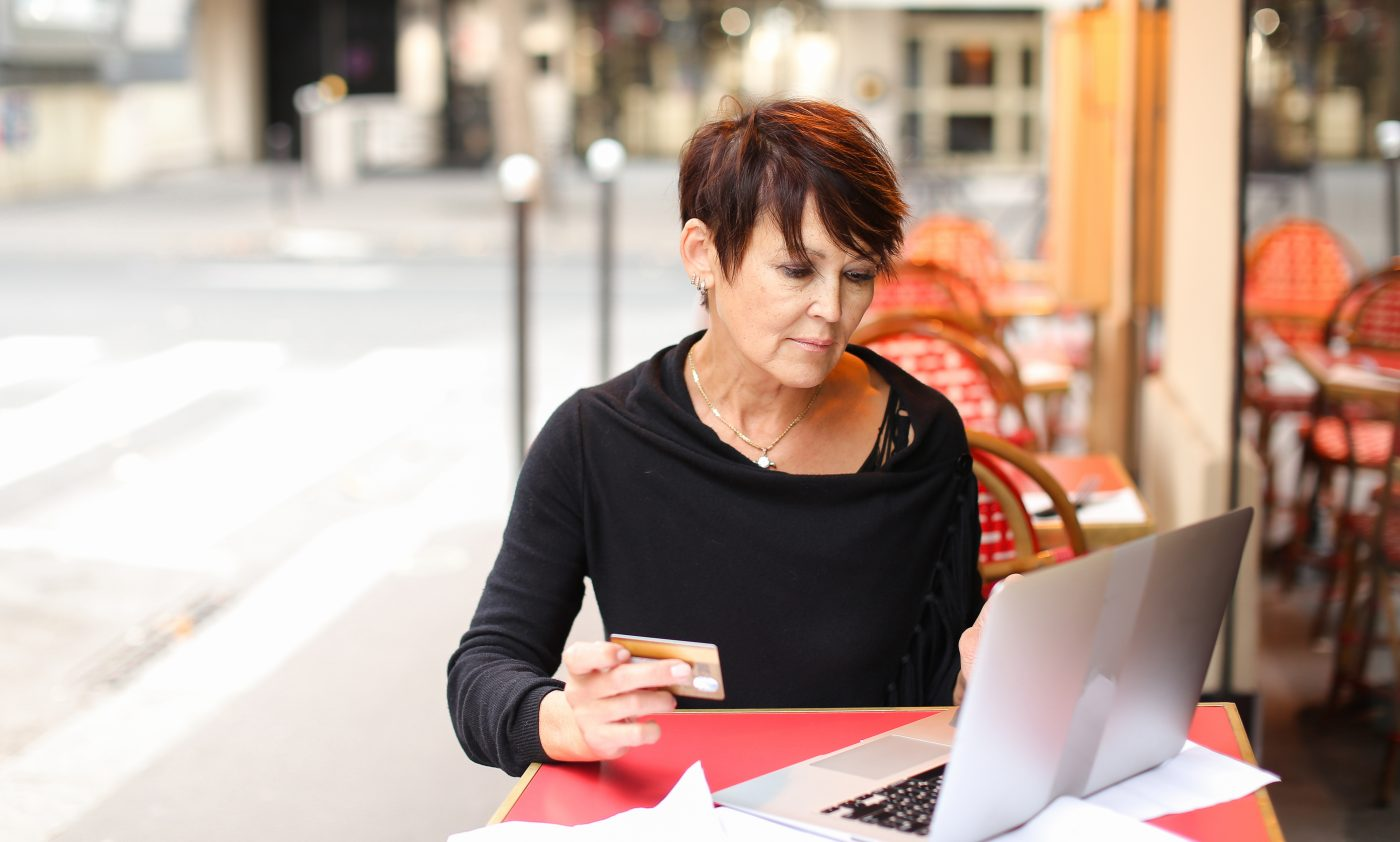 female client of co-working working at table with laptop and make purchases by credit card. Aged lady sitting near desk littered with papers glasses laying on sheet. Woman hold card and enters payment information in computer. Concept of easy shopping with gadgets and internet.