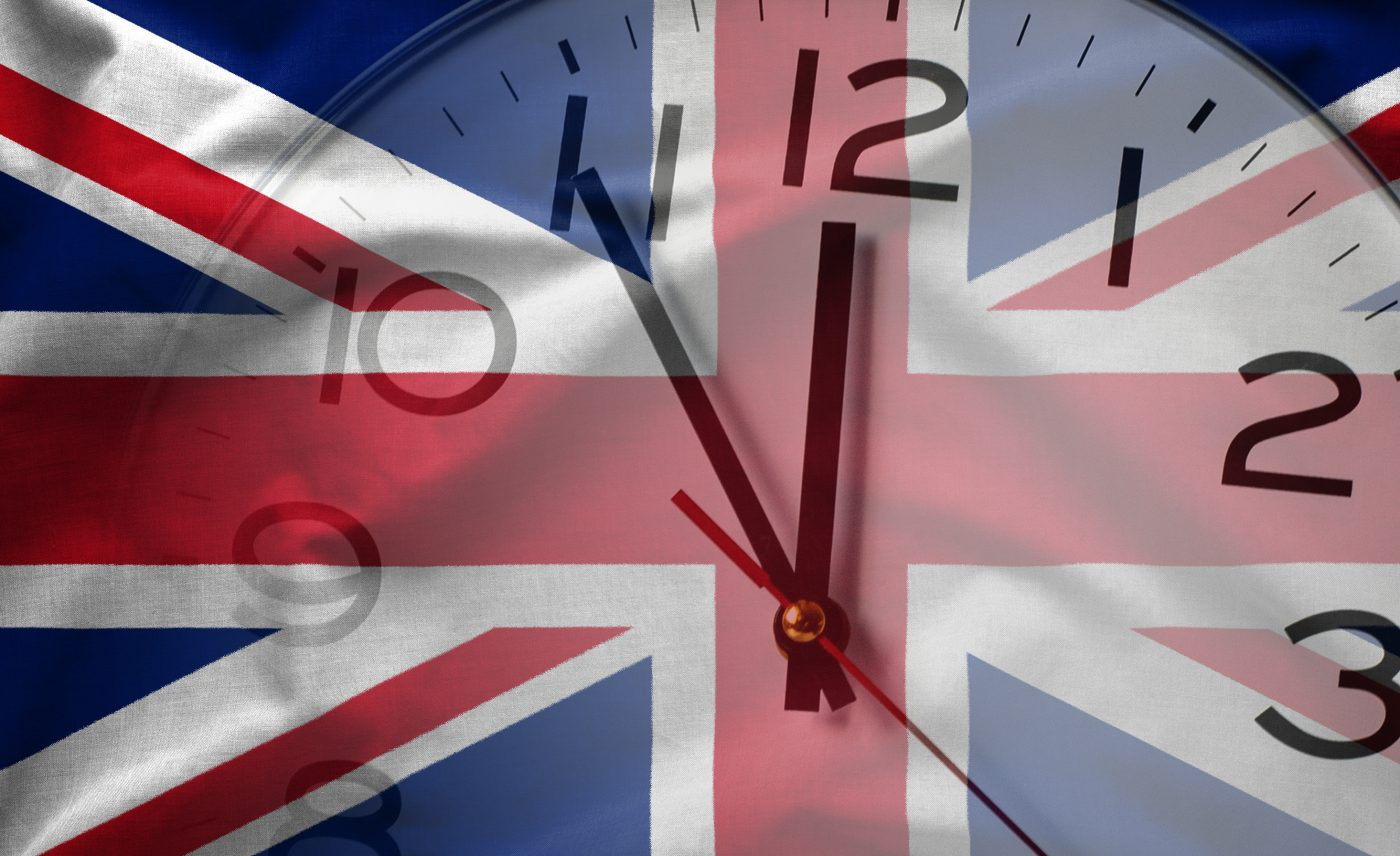 Double exposure of flag of United Kingdom and white clock in concept of Brexit